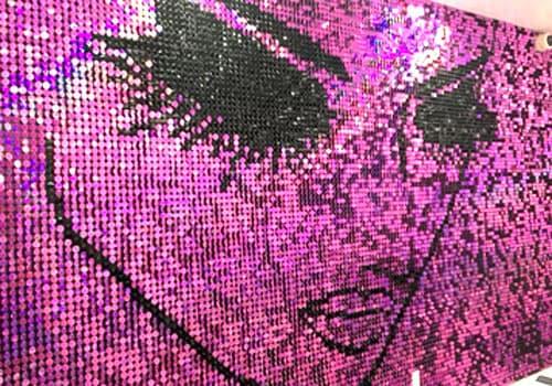Un mur rose avec motif réalisé avec des sequins roses et noirs